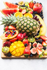 Wall Mural - Healthy raw rainbow fruit platter mango papaya strawberries oranges blueberries pineapple watermelon obn wooden board on light concrete background, top view, selective focus