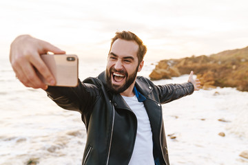 Image of young man taking selfie on smartphone while walking by seaside