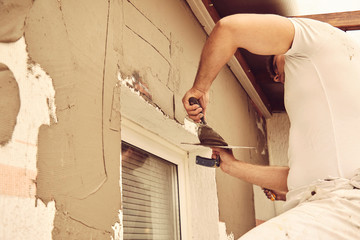 Construction workers plaster a wall.