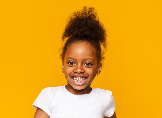 Portrait of african little girl smiling over yellow background
