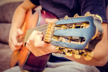 man plays a brown guitar in close-up