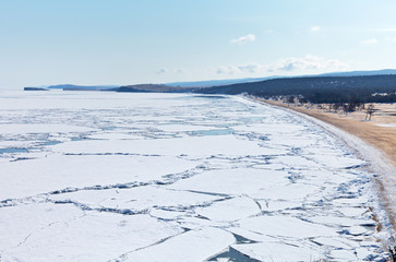 Baikal Lake in the April ice drift. Olkhon Island and the beautiful sandy beach of the Sarayskiy Bay. Spring landscape, change of seasons. Natural background