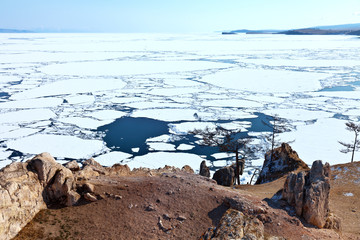 Baikal Lake in spring time. The shores of the Olkhon Island near the village of Khuzhir.  View from Burhan Cape to ice drift on Small Sea Strait. Beautiful spring landscape, natural backgraund