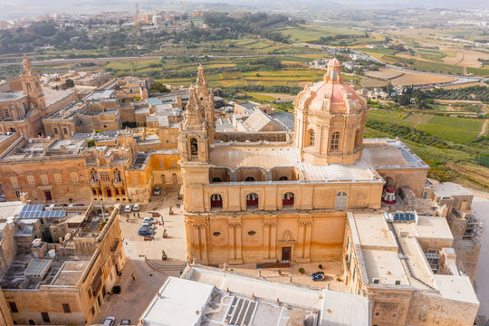 St. Paul's Cathedral in the town of Mdina surrounded by a fortress narrow streets, aerial view.