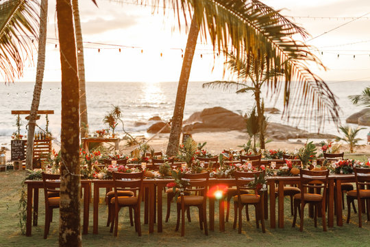 Wooden tables for wedding dinner decorated with tropical flowers, pineapples, coconuts  and glass lamps. View of the ocean. Concept of a tropical destination wedding. in front of the ocean