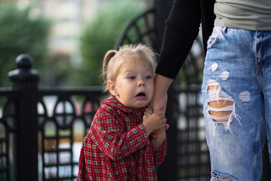 Funny and scared face of the caucasian child of two years old holding mother hand