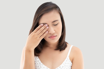 Asian woman suffering from strong eye pain against a gray background. Female has a pain in the eye. Healthcare concept. Having migraine