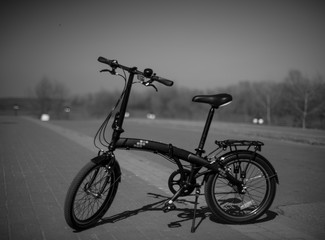 Poster de jardin Velo Black folding bike on the street..
