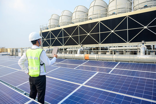 Engineer check condition Solar cell roof top and cooling tower project at industry solar power, Renewable energy Concept.