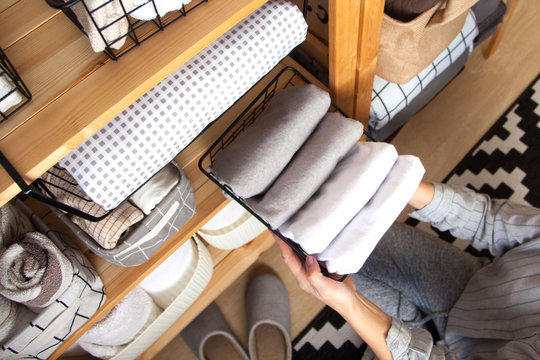 A woman is doing spring cleaning. Folds bedding, blankets, towels and duvet covers in a closet. The concept of housework and storage.