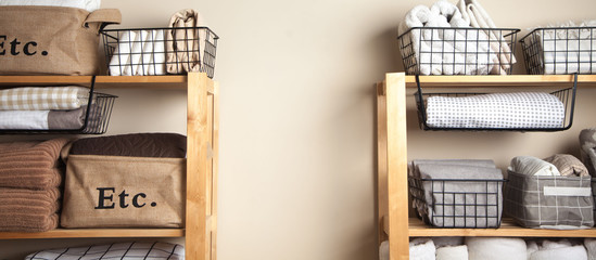 Bed sheets, duvet covers and towels are folded vertically. Metal and fabric black baskets. The concept of housework and storage.
