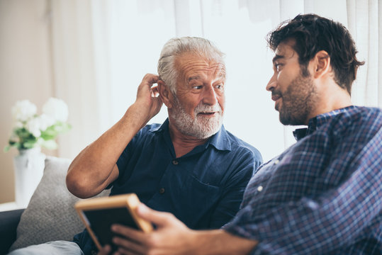 An adult hipster son and old senior father stay for work at home, two generations have a beard talking together and relaxing with smile, happy and enjoy living to isolation quarantine at home