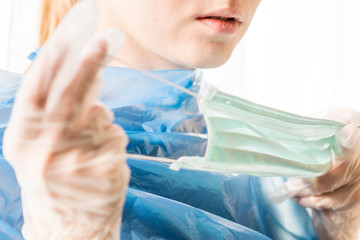 young caucasian woman puts on a sanitary mask, protective gloves and apron, to prevent Coronavirus from Wuhan spreading