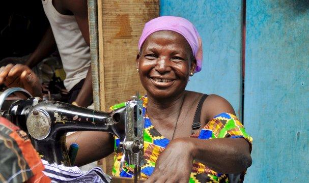 Lächelnde ältere Schneiderin an ihrer Nähmaschine