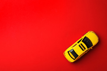 Yellow taxi car model on red background, top view. Space for text