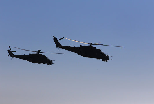 military helicopters fly in the blue sky