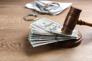 Dollar bills and gavel on wooden table. Bribe concept