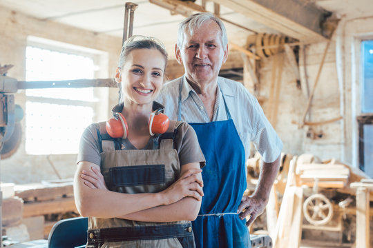 Senior master carpenter with his granddaughter in the wood workshop