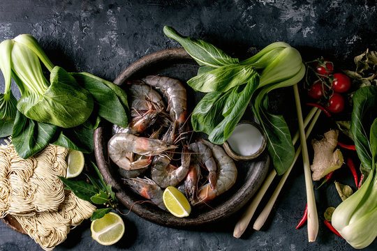 Raw prawns shrimp with asian noodles, cocnut milk and vegetables. Ingredients for cooking asian dinner or thai soup tom yum. Dark concrete background. Flat lay, space