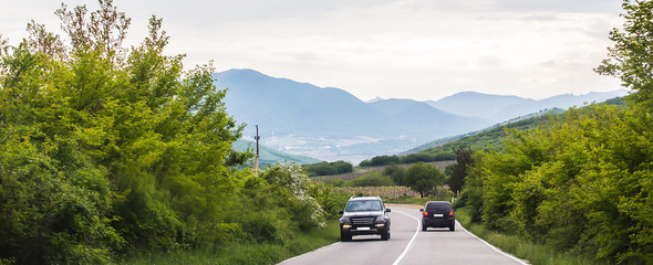 Cars move along a winding highway in the highlands