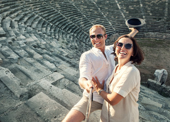 Couple take summer vacation photo with selfie stick in the ancient Theatre arena Side Antik Tiyatro,Turkey.