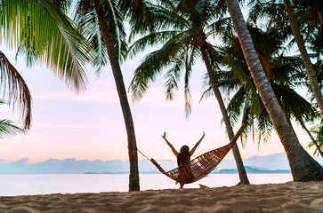 Young woman meeting morning sunrise sunlight sitting in a hammock and lazy stretching her body raising arms up on the sandy beach under the palm trees. Calm exotic places vacation concept image.