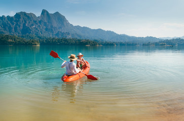 Mother and son floating on kayak together on Cheow Lan lake in Thailand. Traveling with kids concept image.