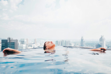 Young female relaxing in top roof infinity swimming pool with city view to the modern business center downtown with a skyscrapers and towers. Luxury vacation concept image.