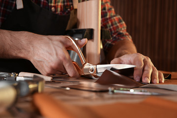 Man cutting leather with scissors at table, closeup