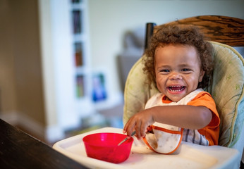 Cute Laughing diverse Child sitting in his high chair eating a meal. Happy expression as he eats a bowl of food while wearing a bib