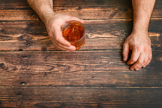 A man raises a glass of alcohol in the hope of a drink for intoxication. The concept of alcoholism and alcohol dependence.