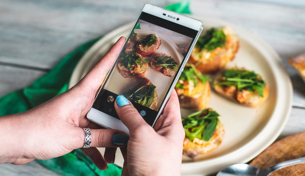 a person takes pictures with her phone, photographs healthy food