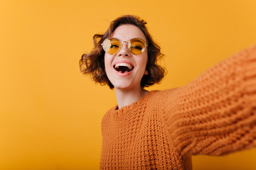 Laughing magnificent woman in funny yellow sunglasses making selfie. Studio portrait of relaxed white girl in knitted sweater taking picture of herself.