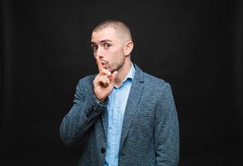 young businessman asking for silence and quiet, gesturing with finger in front of mouth, saying shh...