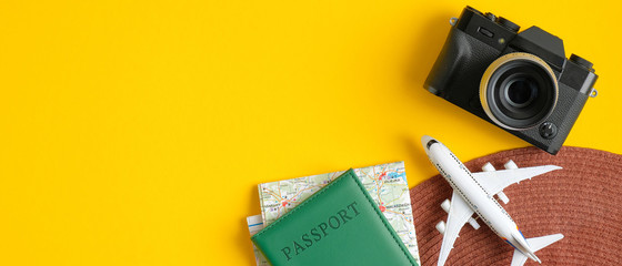 Top view of traveler accessories. Flat lay beach hat, passport, map, airplane, photo camera on yellow background with copy space. Travel summer holiday vacation banner concept
