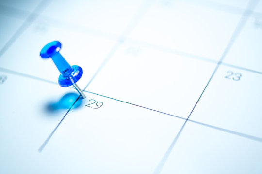 Blue push pin on calendar 29th leap year day of the month