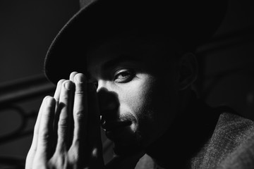 Close-up photo of interested african man posing in the dark. Black and white shot of confident guy in stylish hat.