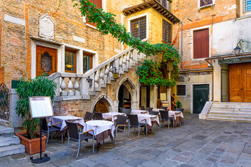 Keuken foto achterwand Venetie Old street with tables of restaurant in Venice, Italy. Architecture and landmark of Venice. Cozy cityscape of Venice.