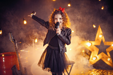 Beautiful girl with curly hair wearing leather jacket, boots sing into a wireless microphone for karaoke like rock star in recording studio or stage. Smoke on background.