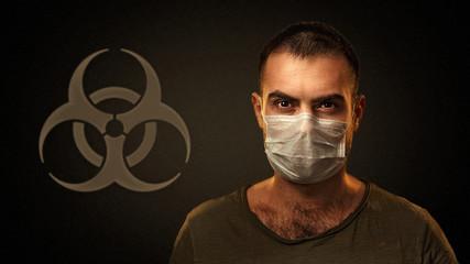 Portrait of caucasian man wearing protective mask against the coronavirus and biohazard symbol on...