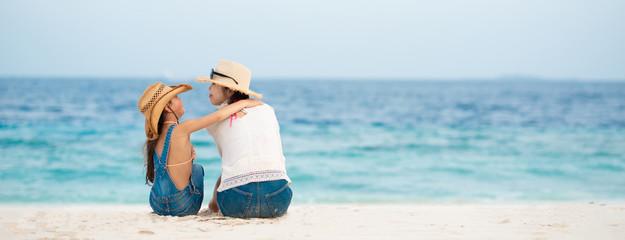 砂浜に座って話す母と娘