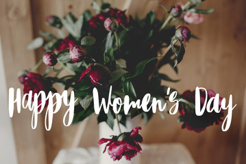 Happy women's day text on stylish peony bouquet in white vase on rustic wooden background. Red and pink peonies rural still life. greeting card