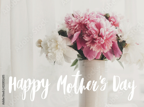 Happy Mother's day text handwritten on lovely peony bouquet in sunny light on rustic window sill. Stylish pink and white peonies in vase. Happy Mothers day greeting card