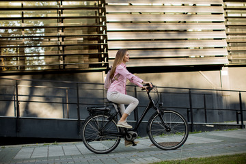 Young woman riding e bike in urban enviroment Fototapete