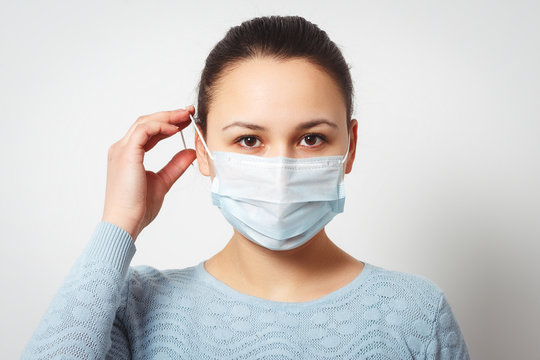 Studio portrait of young woman wearing a face mask, looking at camera, close up, isolated on gray background. Flu epidemic, dust allergy, protection against virus