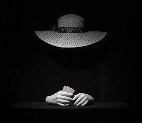 The Ghost of a woman in an elegant hat with playing cards in her hands on a black background. The...