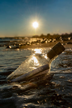 Bottle with a message in the sea at sunset