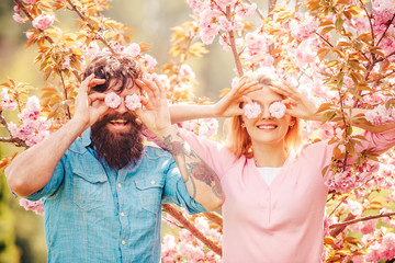 Smiling couple in love on blossoming tree garden background. Man Couple near sakura tree. Happy easter. Hunting Egg.