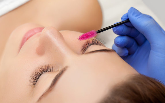 Eyelash extension procedure close up. Beautiful woman with long eyelashes in a beauty salon. Makeup concept