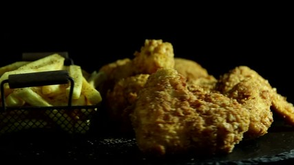 Fototapete - Breaded crispy fried chicken legs and wing, french fries, sauce,  rotation 360 degrees.